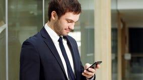 Portret van een jonge succesvolle zakenman die een smartphone in modern bureau gebruiken stock video