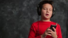 Portret van een jonge tiener Hij luistert aan muziek in de hoofdtelefoons stock videobeelden