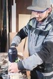 Portret van een jonge timmermansschrijnwerker met elektrische malensnijder in de handen van een arbeider in een huisworkshop aanv stock foto's
