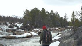 Portret van een jonge toerist met een rugzak Mening van de rug Op de achtergrond een rivier, bos, bergen, blauwe hemel stock footage
