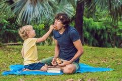 Portret van een jonge vader en zijn zoon die van een hamburger in een park en het glimlachen genieten royalty-vrije stock fotografie