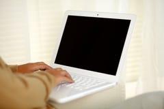 Jonge vrouw die aan laptop computer werken Royalty-vrije Stock Foto's