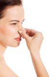 Portret van een jonge vrouw die haar neus houden. stock afbeeldingen