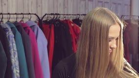 Portret van een jonge vrouw die in een spiegel in een kledingsopslag kijken stock footage