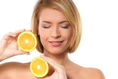 Portret van een jonge vrouw die twee sinaasappelen houdt Royalty-vrije Stock Afbeeldingen