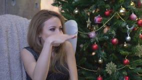 Portret van een jonge vrouw die in vakantiekleren ver weg met hand haar voorhoofd op de achtergrond van de Kerstmisboom bekijken stock video