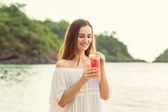 Portret van een jonge vrouw die een verse watermeloencocktail op tropisch strand houden royalty-vrije stock afbeeldingen