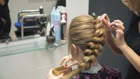Portret van een jonge vrouw in een schoonheidssalon: het creëren van het prachtige plaatsen van krullen Een blonde in een kapper  stock videobeelden