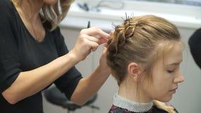 Portret van een jonge vrouw in een schoonheidssalon: het creëren van het prachtige plaatsen van krullen Een blonde in een kapper  stock video