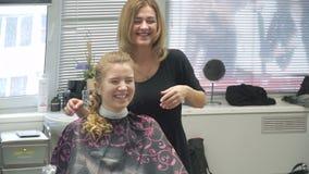 Portret van een jonge vrouw in een schoonheidssalon: het creëren van het prachtige plaatsen van krullen Een blonde in een kapper  stock footage