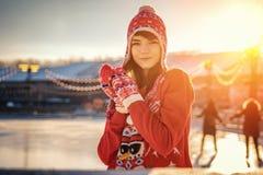 Portret van een jonge vrouw in een hoed op de ijsbaan, een glimlach op zijn gezicht, de zon stock afbeelding
