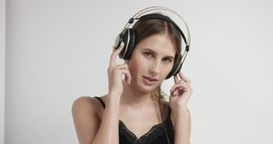 Portret van een jonge vrouw in hoofdtelefoons stock video