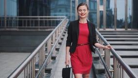Portret van een jonge vrouw in een jasje en het dragen van een aktentas in haar handen zelfverzekerde bedrijfsvrouw in een rood stock footage