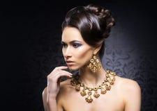 Portret van een jonge vrouw in juwelen en make-up stock foto's