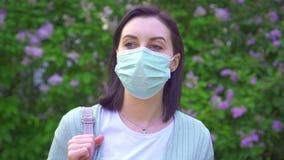 Portret van een jonge vrouw in een medisch masker op de achtergrond van bloeiende installaties in het Park stock videobeelden