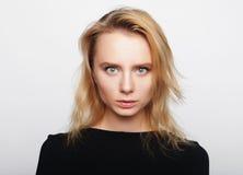 Portret van een jonge vrouw met blond haar in een zwart overhemd op a stock foto