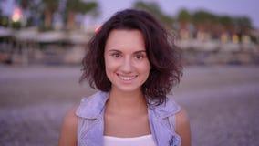 Portret van een jonge vrouw met kort en krullend haar dat gekleed in een denim is en zich op het strand in de zomer bevindt stock video
