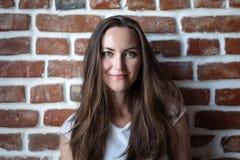 Portret van een jonge vrouw op een rode bakstenen muurachtergrond stock foto's