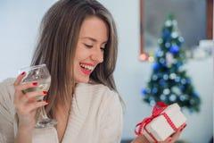 Portret van een jonge vrouw tijdens voorbereidingen voor Kerstmis thuis Toothy glimlachende vrouw die met rode lippen giftdoos en Stock Foto's