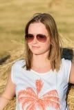 Portret van een jonge vrouw in zonnebril die op een baal van hooi leunt Stock Foto