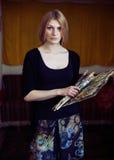 Portret van een jonge vrouwenschilder met een palet en borstels Stock Afbeeldingen
