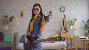 Portret van een jonge vrouwentuimelschakelaar die emotioneel de elektrische gitaar spelen stock footage