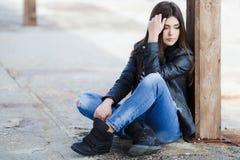 Portret van een jonge vrouwenzitting op de stoep Stock Foto's