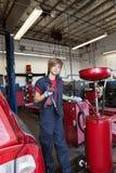 Portret van een jonge werktuigkundige die zich door lassenmateriaal bevinden stock afbeelding