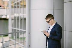 Portret van een jonge zakenman die op zijn tabletpc zien op s Royalty-vrije Stock Foto's