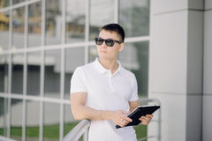 Portret van een jonge zakenman die tabletpc op de straat houden Royalty-vrije Stock Afbeeldingen