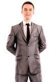 Portret van een jonge zakenman met handen bij rug stock afbeeldingen