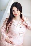 Portret van een jonge zwangere vrouw in een roze kleding tegen een witte muur die de camera bekijken Zwangerschap Stock Afbeelding