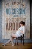 Portret van een jonge zwangere vrouw in wit overhemd in fotostudio Stock Foto