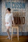 Portret van een jonge zwangere vrouw in wit overhemd in fotostudio Stock Fotografie