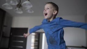Portret van een jongen die op het bed springt Hij die gelukkig en zijn handen golven lachen Langzame Motie stock videobeelden