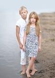 Portret van een jongen en een meisje op het strand Stock Foto