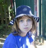 Portret van een Jongen met Blond Haar in Blauwe Hoed Stock Foto