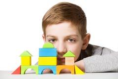 Portret van een jongen met huis van houten blokken wordt gemaakt dat Stock Fotografie