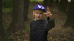 Portret van een jongen met een pennyboard Een kerel van Europese verschijning houdt een stuiverraad in zijn handen en glimlacht D stock videobeelden