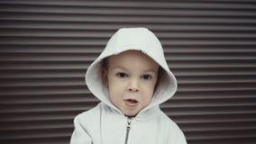 Portret van een jongen van twee jaar op een achtergrond van bruine texturen stock footage