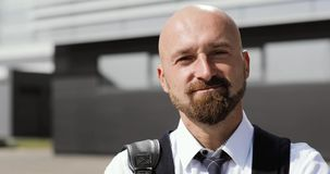 Portret van een kale mens met een baard op de achtergrond van een bureaugebouw stock videobeelden