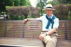 Portret van een kerelzitting op een parkbank royalty-vrije stock afbeeldingen