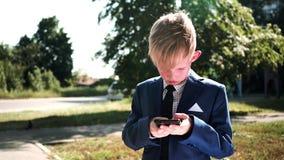 Portret van een kind die met een smartphone spelen Nadruk op smartphone stock videobeelden