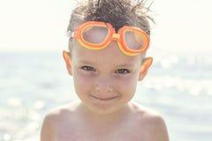 Portret van een kind in glazen voor het zwemmen tegen het overzees Jong geitje in bril voor het zwemmen bij het overzees Portret  stock fotografie