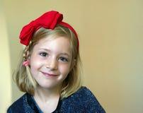 Portret van een klein blondemeisje met een rode boog op zijn hoofd stock foto's