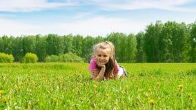 Portret van een klein meisje dat op een groene weide in vers gras ligt Het concept van de zomer Selectieve nadruk De ruimte van h stock afbeelding