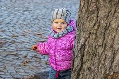 Portret van een klein meisje dat uit van achter een boom in Au kijkt Royalty-vrije Stock Afbeeldingen