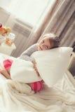 Portret van een klein meisje die een hoofdkussen koesteren Royalty-vrije Stock Foto's