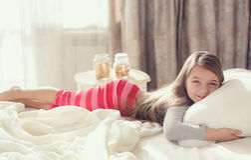 Portret van een klein meisje die een hoofdkussen koesteren Royalty-vrije Stock Fotografie