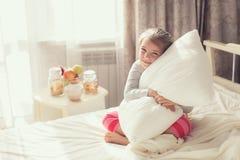 Portret van een klein meisje die een hoofdkussen koesteren Royalty-vrije Stock Foto